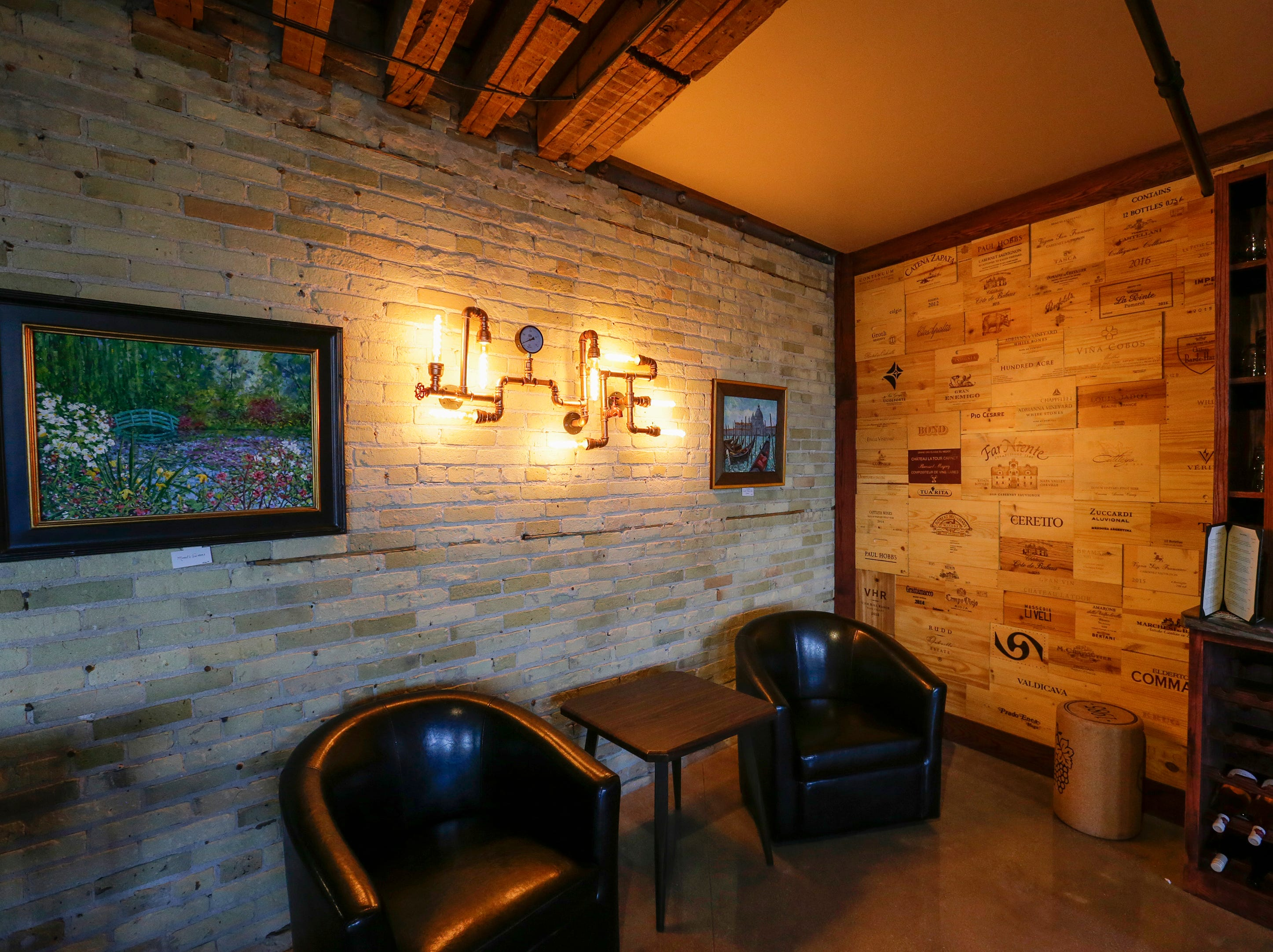 Paintings by Bob Beck adorn the walls along handmade finishes created by the owners at the Waterfront Wine Bar Saturday, May 4, 2019, in Manitowoc, Wis. Joshua Clark/USA TODAY NETWORK-Wisconsin