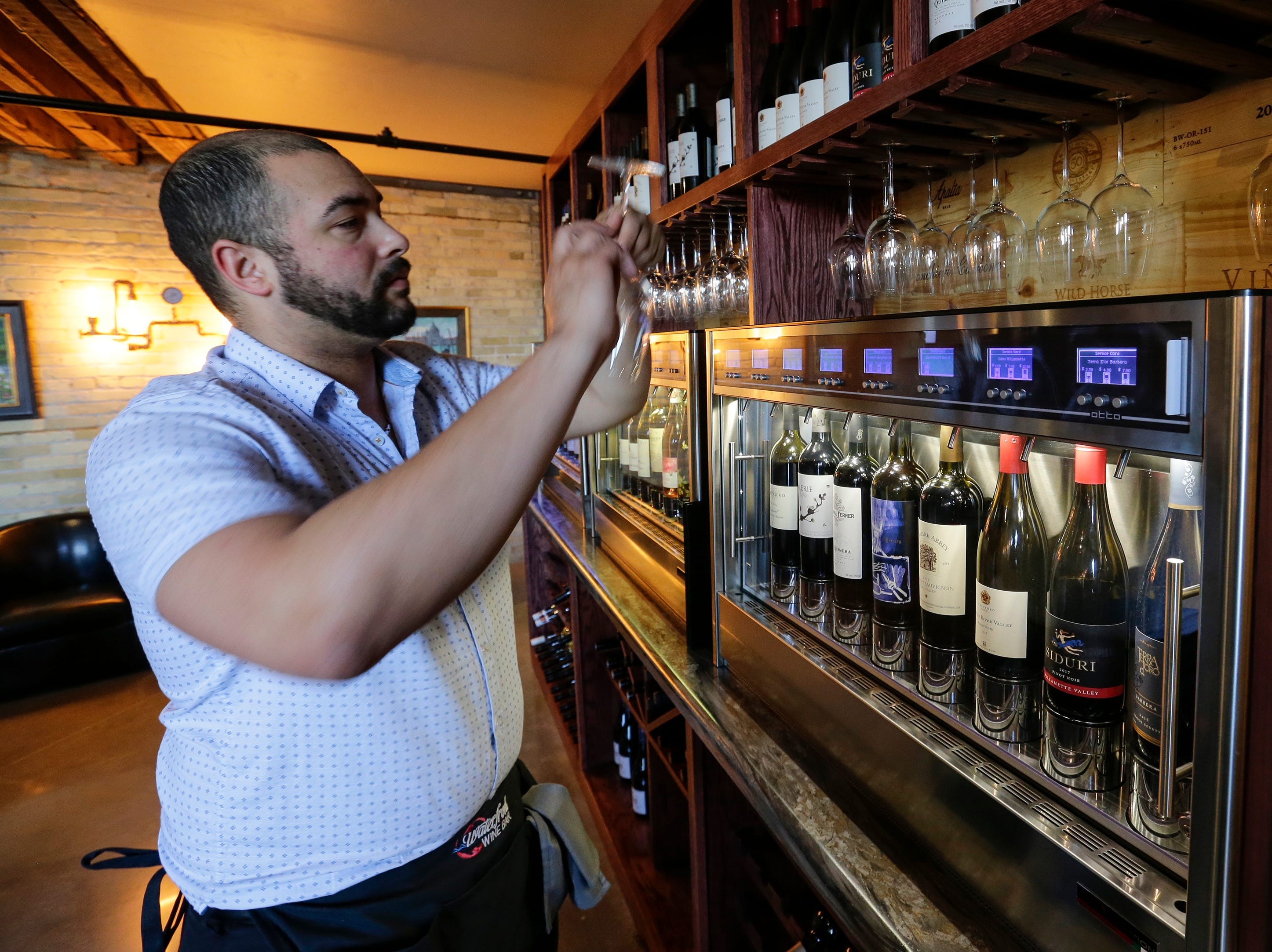 Rick Hoeltke inspects a glass before pouring from the self-serve wine machine at the Waterfront Wine Bar Saturday, May 4, 2019, in Manitowoc, Wis. Joshua Clark/USA TODAY NETWORK-Wisconsin
