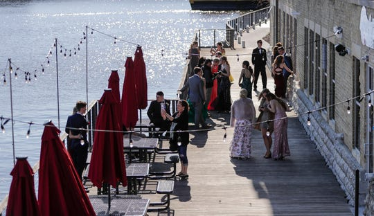 Prom goers gather outside the Waterfront Wine Bar for photo ops near the Manitowoc River Saturday, May 4, 2019, in Manitowoc, Wis. Joshua Clark/USA TODAY NETWORK-Wisconsin