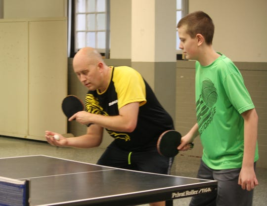 Brian Bayes gets ready to serve while playing doubles with his son, Alex, at the Mansfield Table Tennis Club