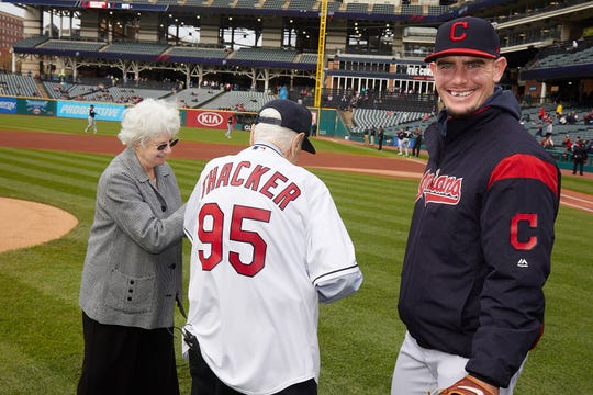 "Ernest ""Pete"" Thacker of Mansfield and his wife Audrey get help from Nick Wittgren of the Cleveland Indians before Pete threw out the first pitch Tuesday night at Progressive Field."