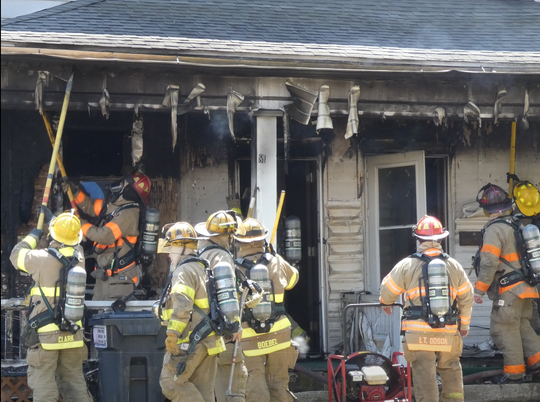 Firefighters battle a blaze at 81-83 W. First St. on Wednesday.