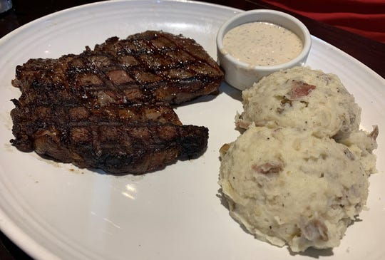 The 13 oz. Tuscan-grilled ribeye with garlic mashed potatoes and a side of garlic aioli from Carraba's, South Naples.