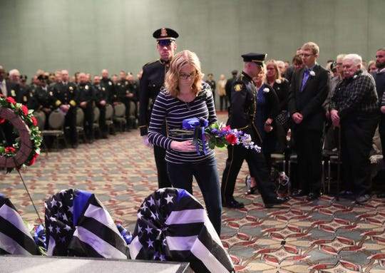 Caroline Rittner lays a memorial wreath of flowers on a chair draped with the law enforcement flag in memory of her husband, Milwaukee Police Officer Matthew Rittner, at the Greater Milwaukee Law Enforcement Memorial Ceremony at the Wisconsin Center on Wednesday. Three empty chairs symbolized three Milwaukee police officers killed in the line of duty  since the 2018 ceremony.