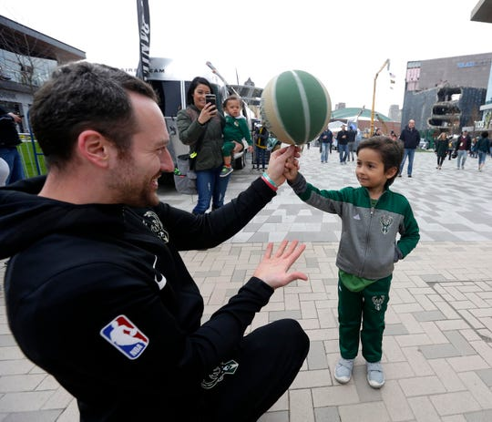 David St. Pierre with the Bucks shows Lincoln Drobac, 5, how to spin a ball on his finger as crowds gather on the plaza before the Milwaukee Bucks vs. Boston Celtics NBA playoff game Wednesday.