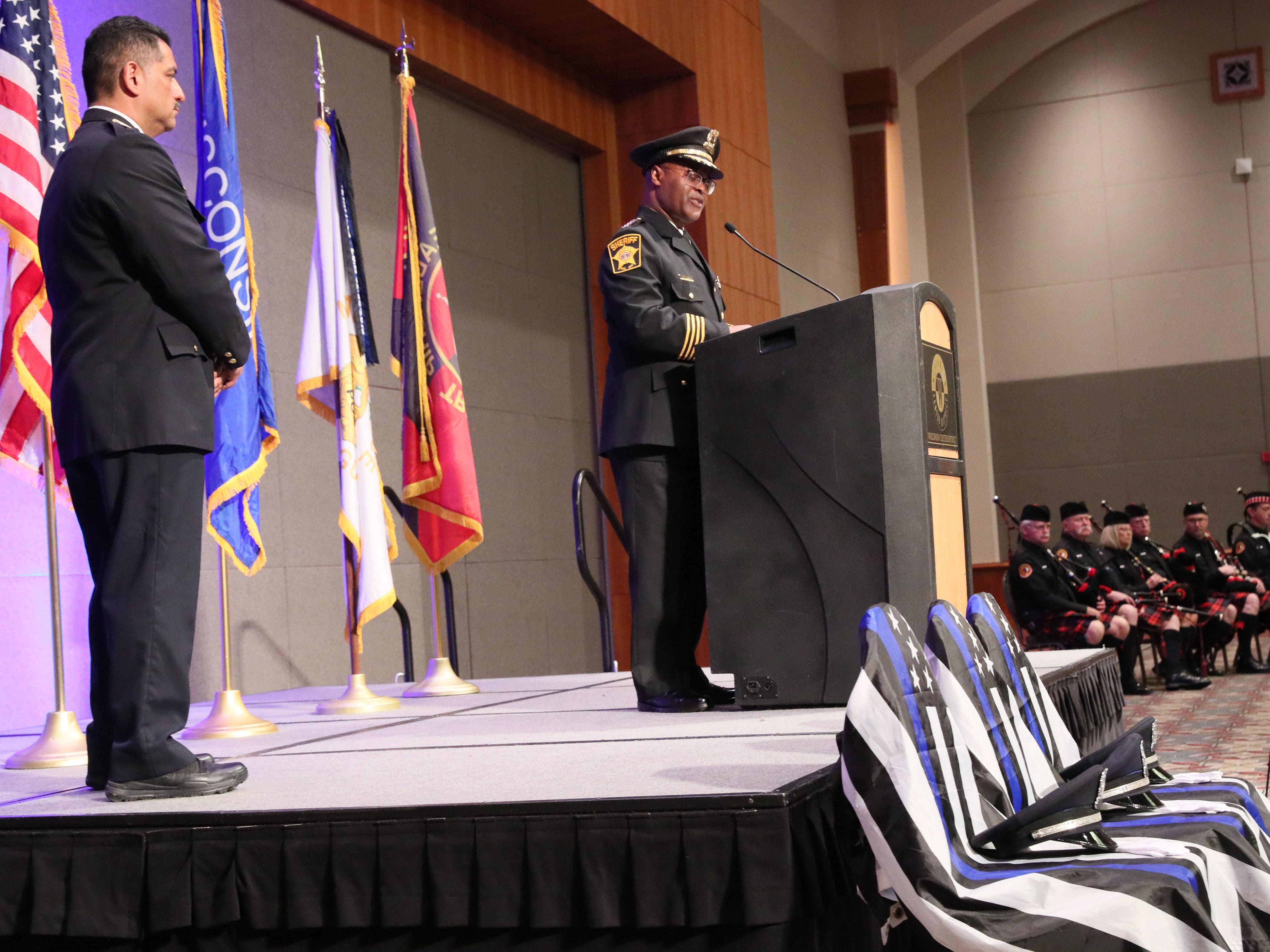 Milwaukee Police Chief Alfonso Morales, left, and Milwaukee County Sheriff Earnell R. Lucas both spoke at the event.  The three chairs in front of the stage draped with the law enforcement flag are in memory of the three officers killed since last year's Law Enforcement Memorial Service.