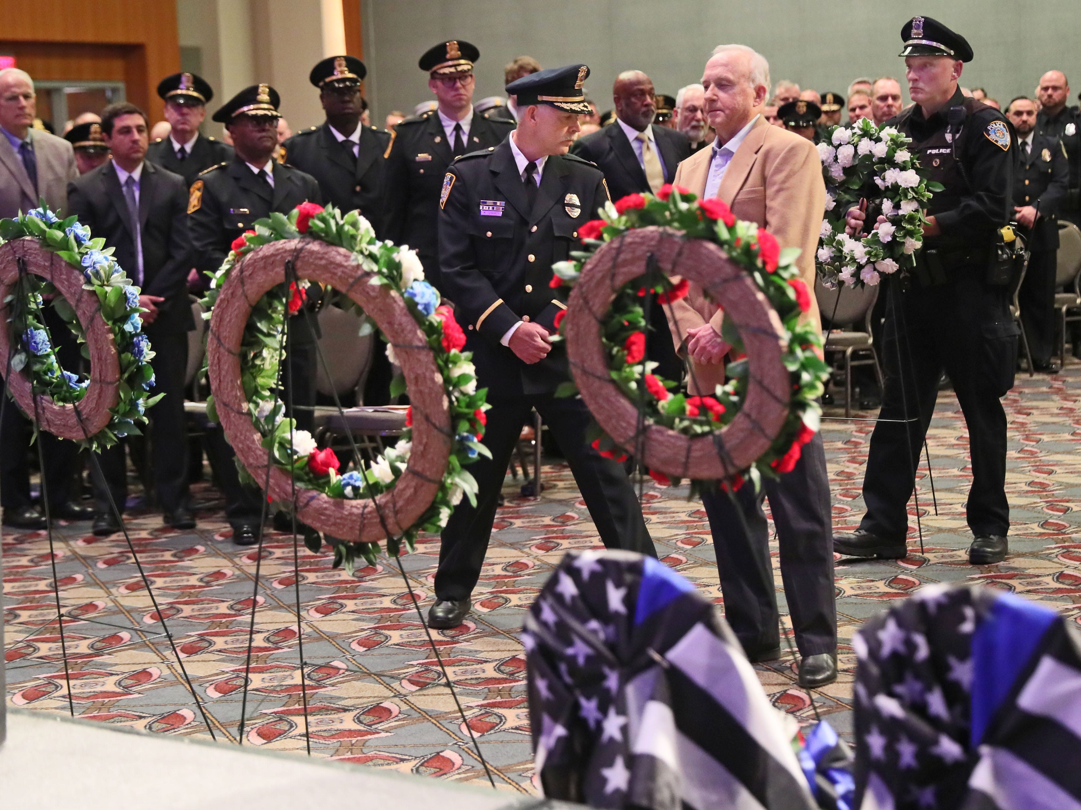 Don Hedbany, center, prepares to lay a wreath in memory of Glendale Police Officer Ron Hedbany. He was accompanied by Police Officer Jeffrey Musialowski, right, and Glendale Chief of Police Mark Ferguson, left.