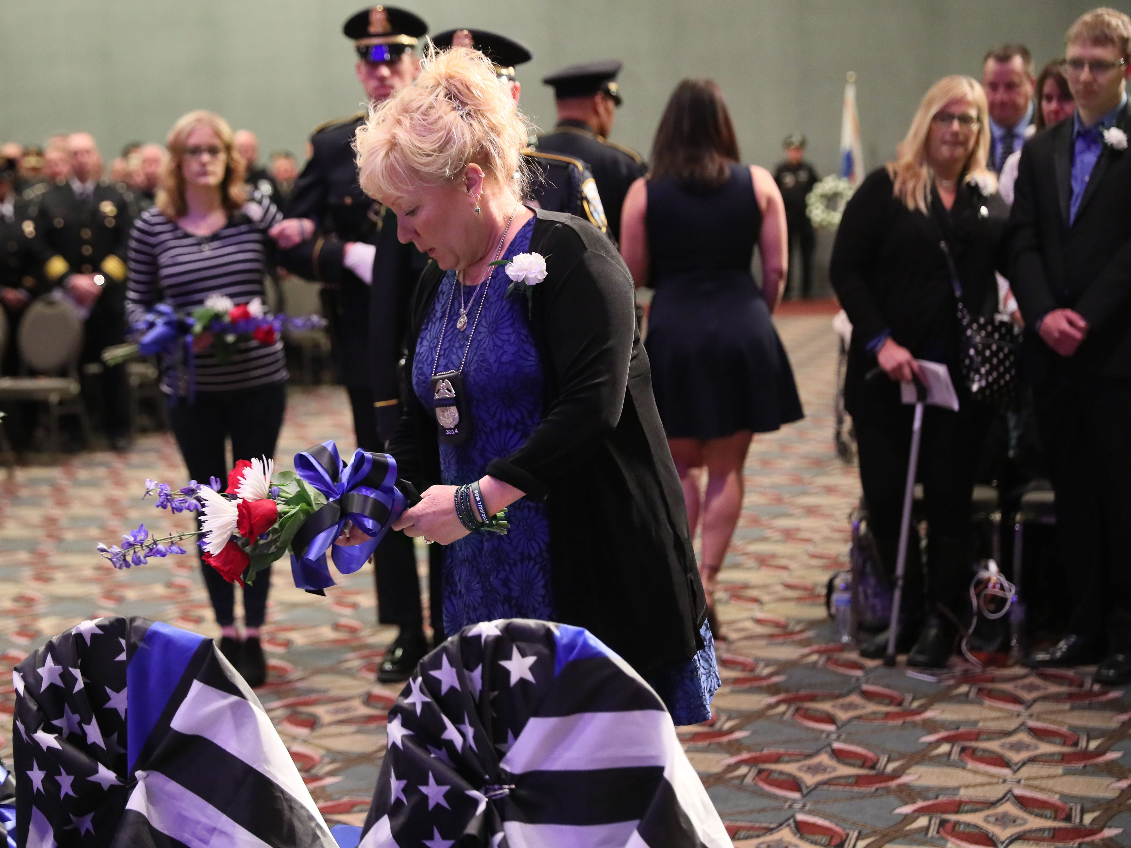 Susan Michalski lays a memorial wreath of flowers on a chair draped with the law enforcement flag in memory of her husband, Milwaukee Police Officer Michael Michalski.