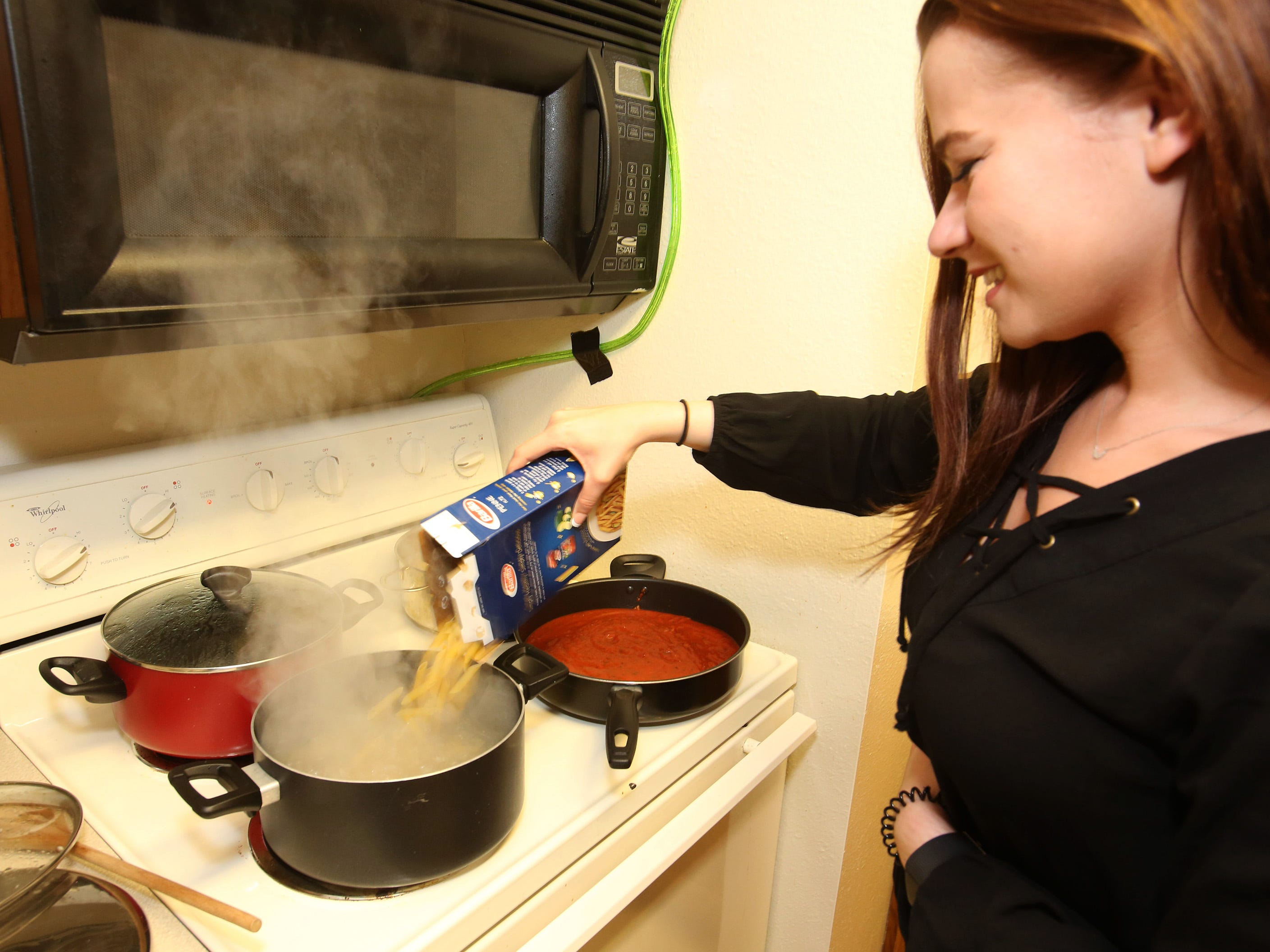 Rachel Witt, a senior in mechanical engineering, prepares the pasta dinner shared with fellow students and faculty in an effort to meet new people.