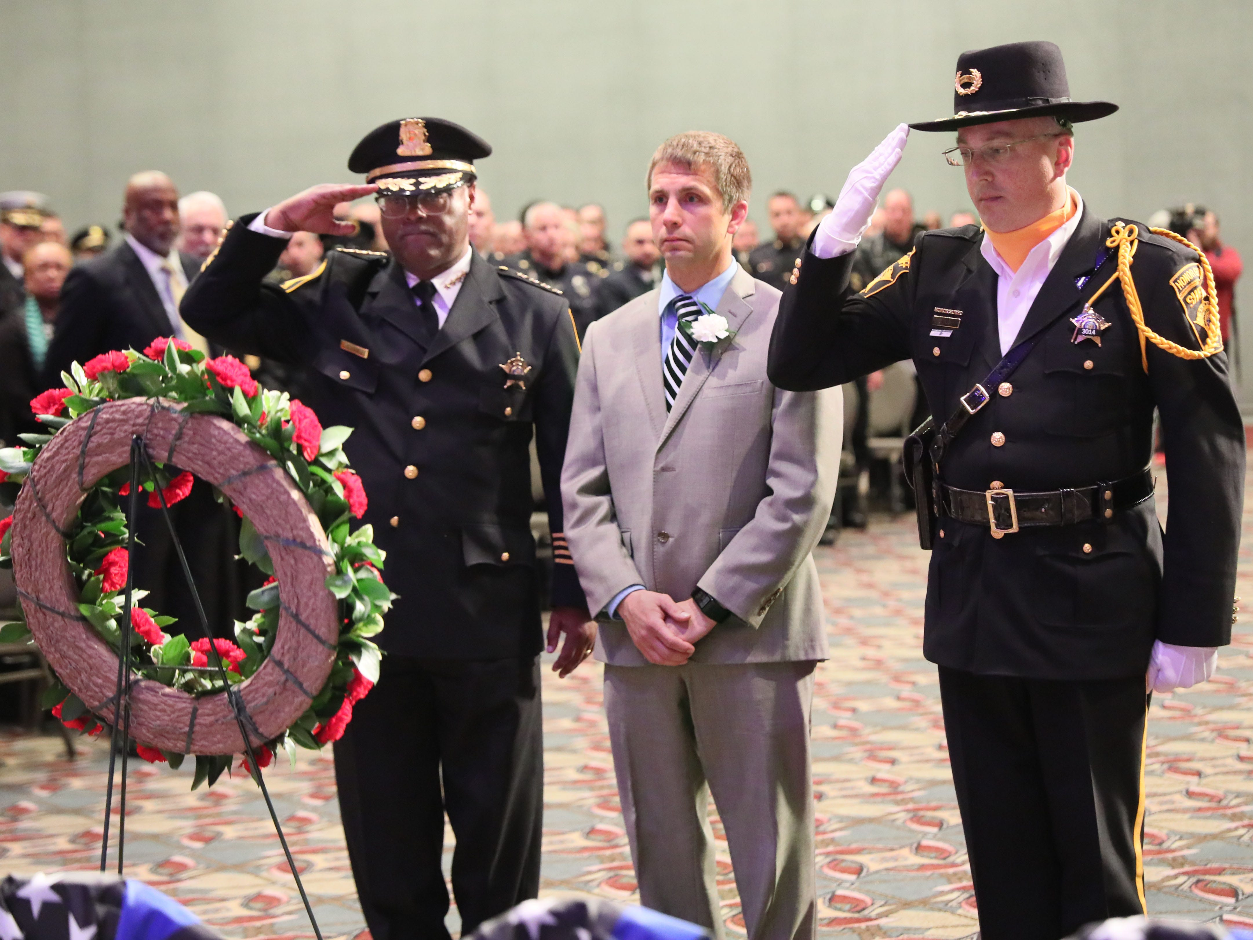 Christopher Demos, center,  accompanied by Sheriff Earnell R. Lucas, left, and Deputy Michael Koch, right, presents a wreath in honor of David Demos of the Milwaukee County Sheriff's Office.