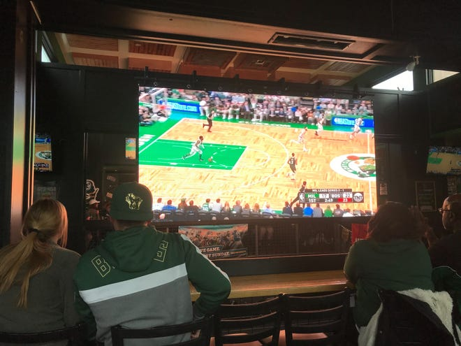Bar-goers watch a Milwaukee Bucks game on a 13-foot-wide screen at Jack's American Pub.