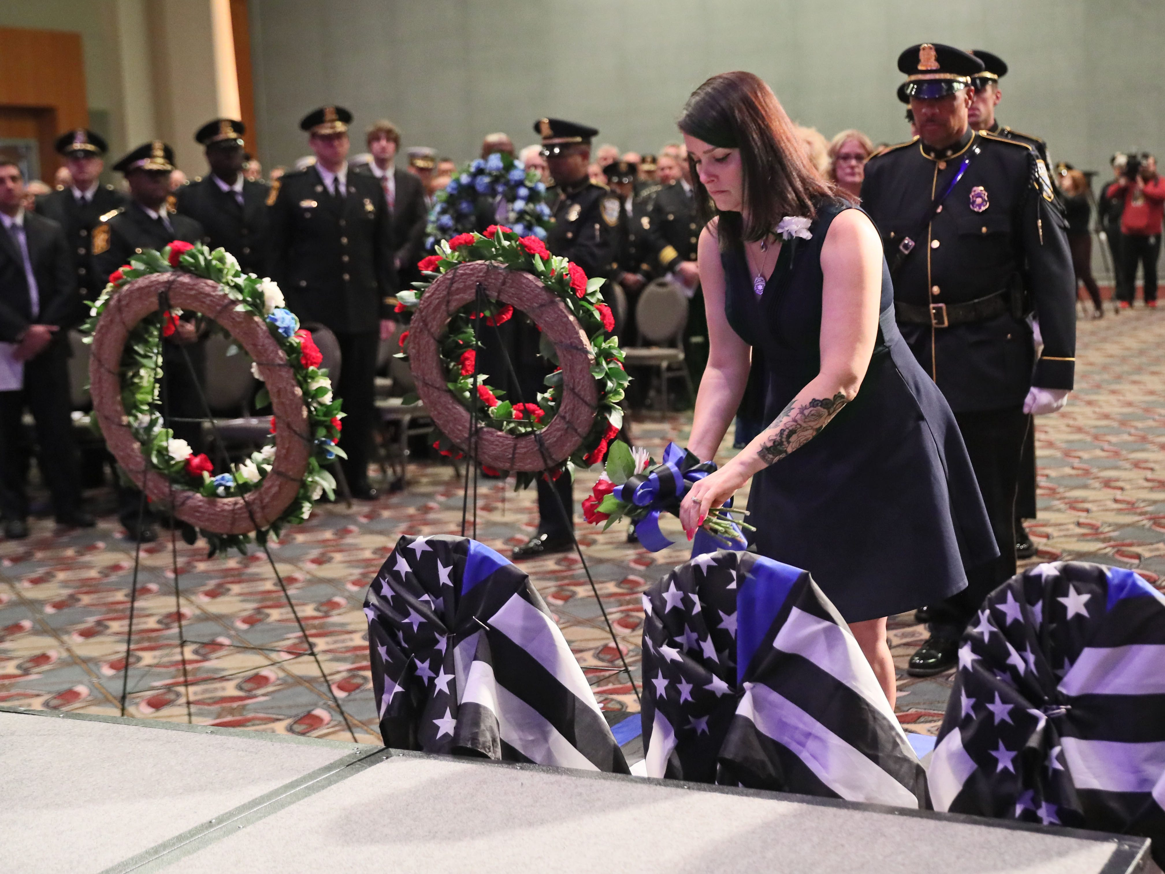 Christy Irvine-Bachman lays a memorial wreath of flowers on a chair draped with the law enforcement flag in memory of Milwaukee Police Officer Charles Irvine Jr.