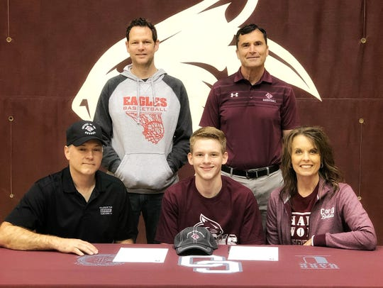 Mountain Home Christian Academy's Cooper Long (front, middle) recently signed a National Letter of Intent to play basketball at College of the Ozarks. Pictured with Long are: (front row) his father Joseph Long, his mother Kim Long, (back row) MHCA coach John Bingham, and College of the Ozarks coach Steve Shepherd.