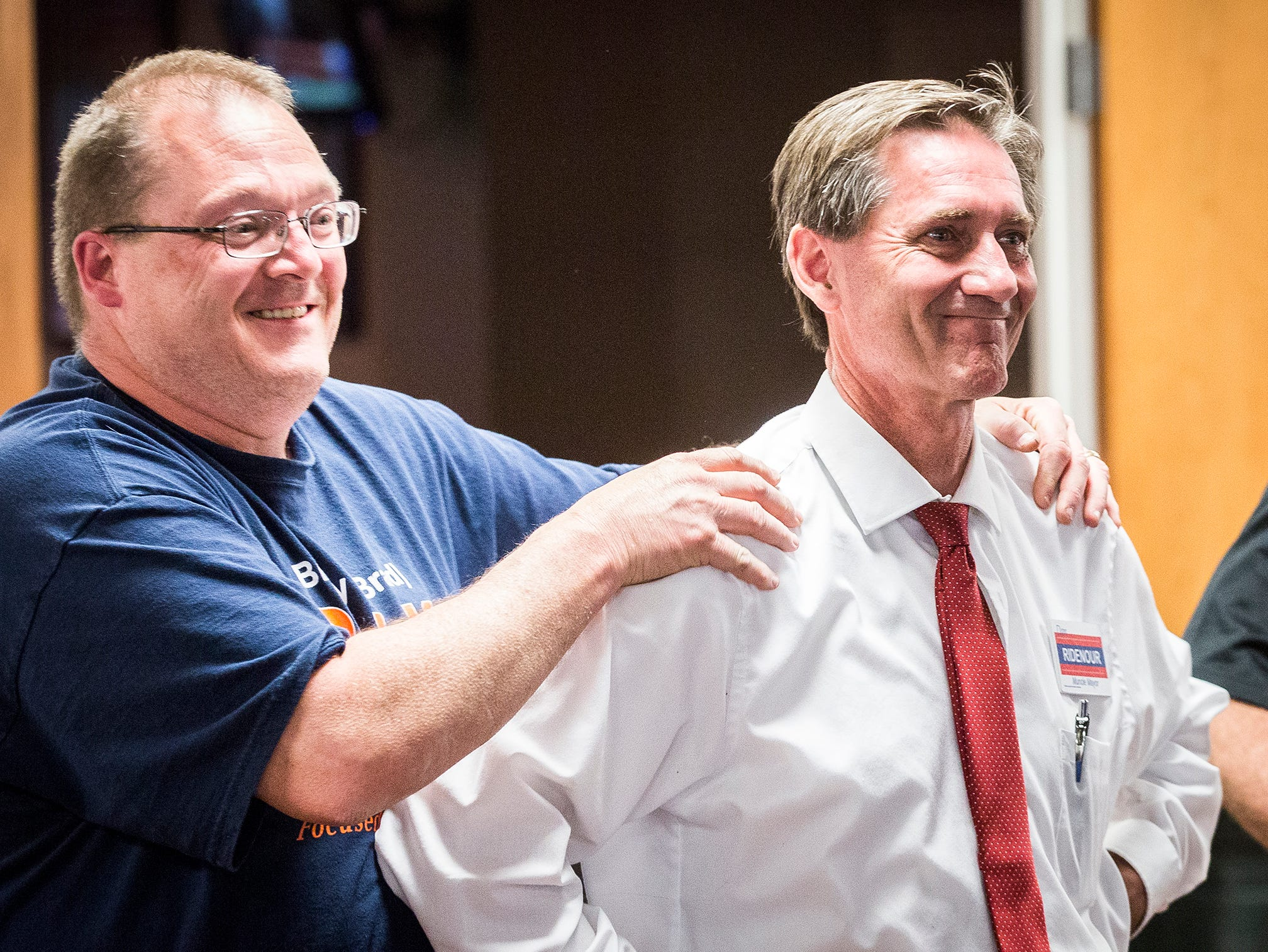 Republican City Council nominee Bradley Polk congratulates mayoral nominee Dan Ridenour at the Knights of Columbus Tuesday night.