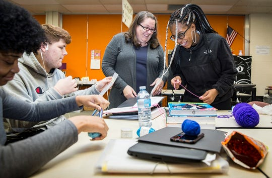 Teacher Angie Abram-Rains works on a fashion design project with students in her classroom at Central Wednesday afternoon.