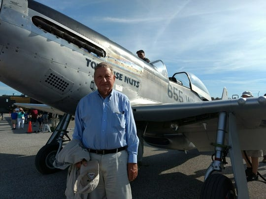 Bill Frazier is shown with a 1943 P51 Mustang WWII fighter plane he flew earlier this year.