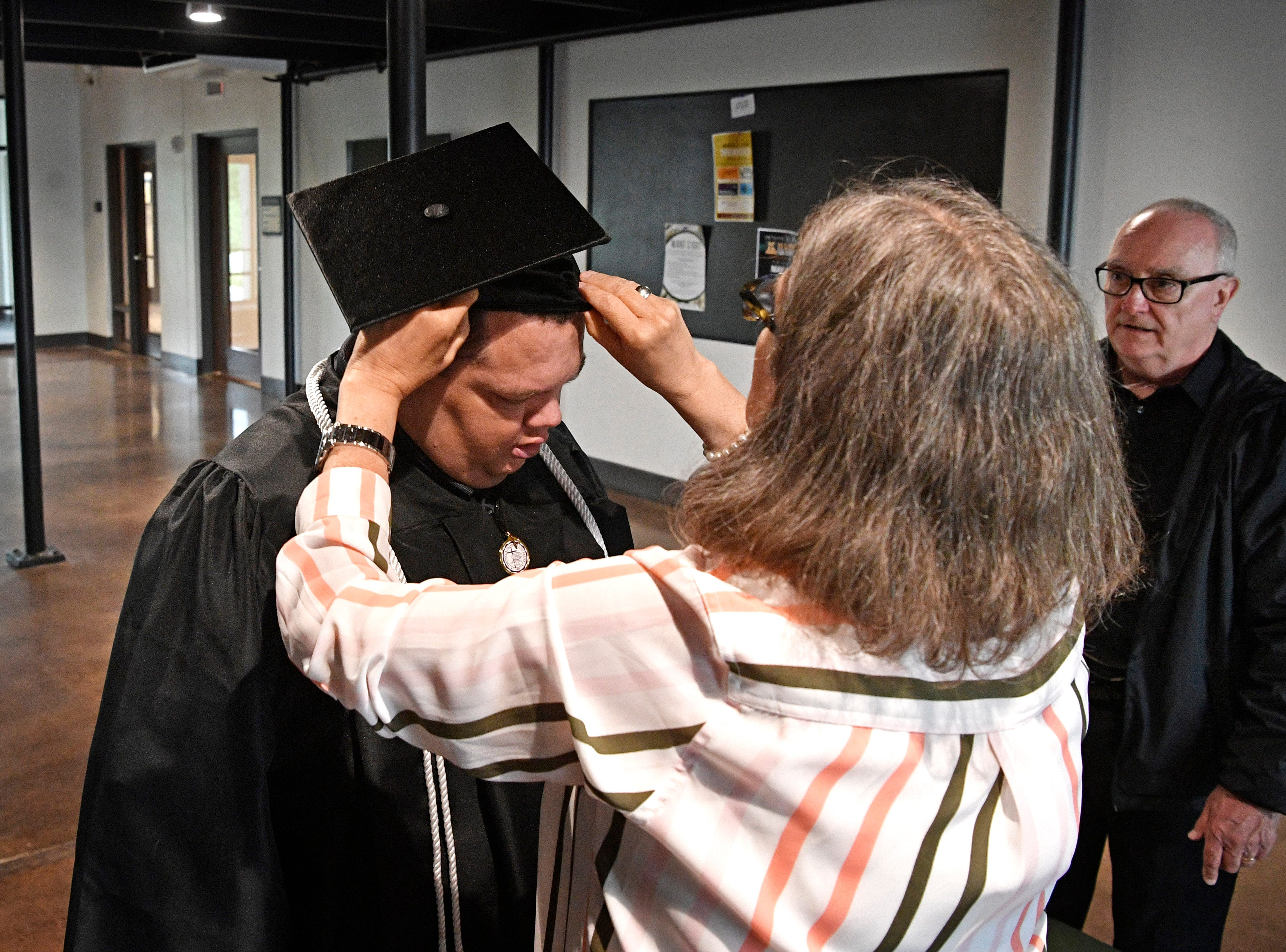 Brian Schnelle has his hat adjusted by Brenda Patterson, Professor, Dept. of Exercise and Sport Science, before he graduated from Trevecca on Saturday after 12 years as a student. He is on the autism spectrum & has pursued his degree for all those years, taking about 6 credits a semester Saturday, May 4, 2019, in Nashville, Tenn.