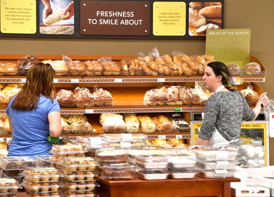 Hope Johnson, right, helps Julie Zamudio pick out bread in the bakery on May 8 at a Publix in Franklin.