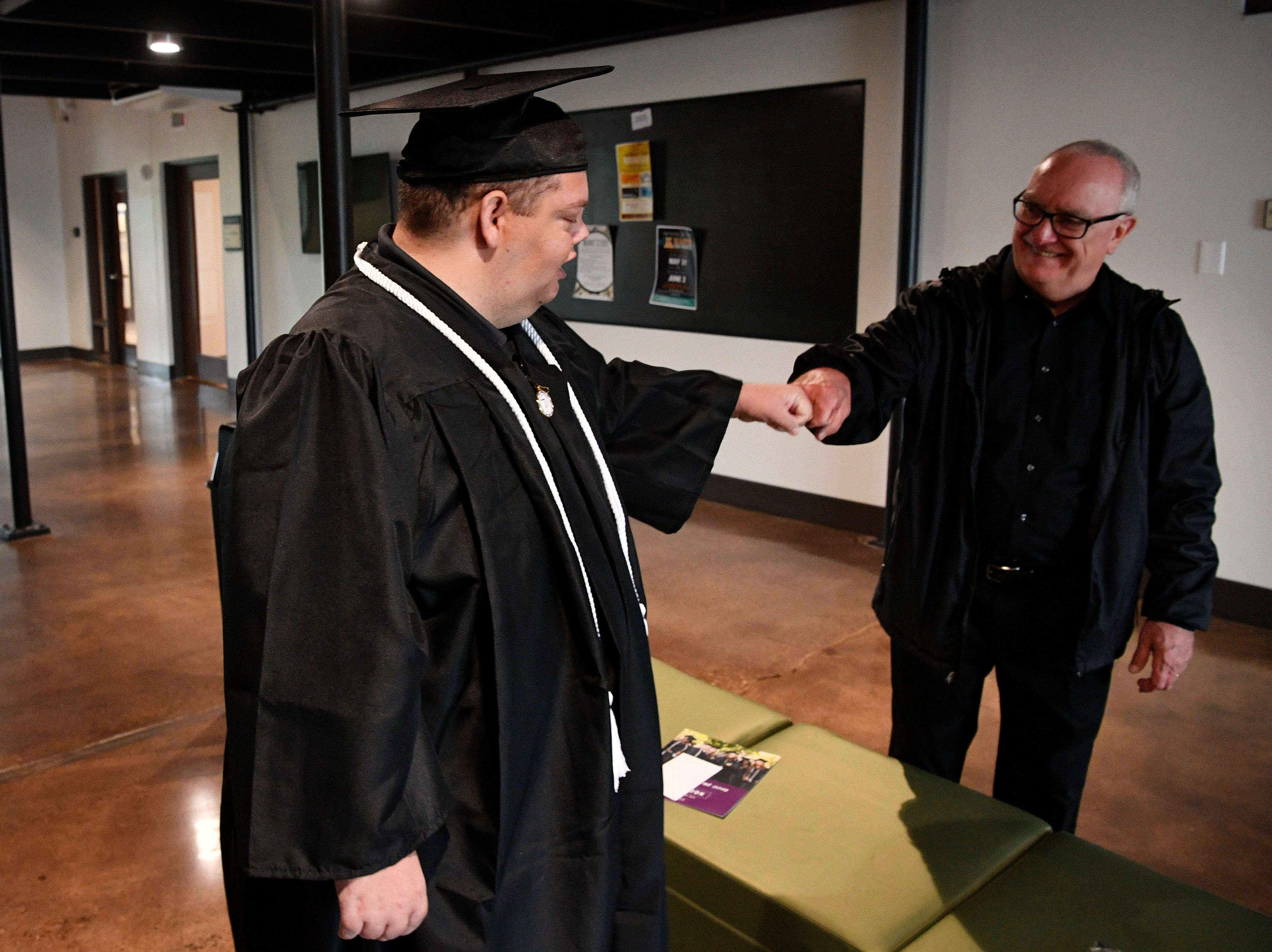 Brian Schnelle gets a fist bump from his father Jeff as he prepares to graduate from Trevecca on Saturday after 12 years as a student. He is on the autism spectrum & has pursued his degree for all those years, taking about 6 credits a semester Saturday, May 4, 2019, in Nashville, Tenn.
