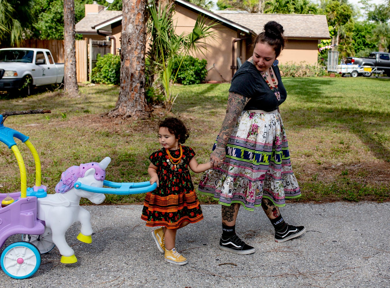 "Dakota Osceola and her daughter Mia walk down the driveway of their home in Naples on May 3, 2019. Many members of their family, including Dakota's mother, brother, and grandparents, live on the same street as Dakota and Mia. ""We have everything we need, and that's each other,"" she said. ""We're trying to be financially independent, trying our best to work as hard as we can to accomplish our goals, and that's really what it's been about since the beginning of the Osceolas."""