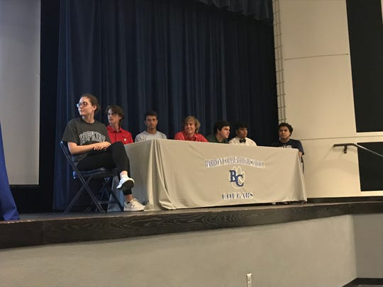 Seven Barron Collier athletes signed to play college sports during a ceremony at the school auditorium Wednesday. From left are Halie Egan (basketball, Johns Hopkins), Thomas Balboni (baseball, Northeastern), Andrew Dreyfuss (baseball, U.S. Merchant Marine Academy), Matt Lord (baseball, Northeastern), Ryan Bloch (football, Dartmouth), Sebastian Torres (football, Jacksonville) and Cipriano Martinez (cross country, Queens University).