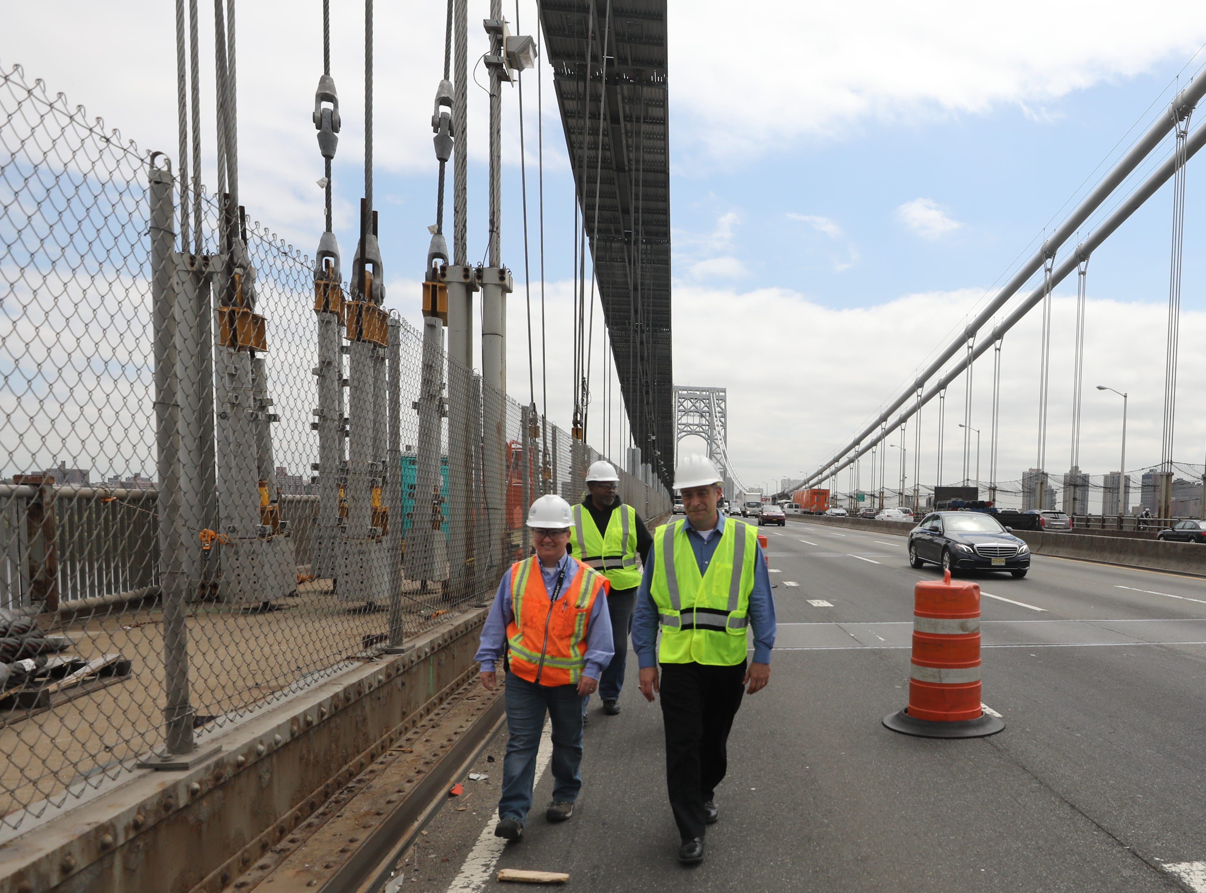Amanda Rogers, lead engineer on the Restore the George program and Ken Sagrestano, general manager of the George Washington Bridge walk along the roadway past the large construction project on the north side of the bridge.