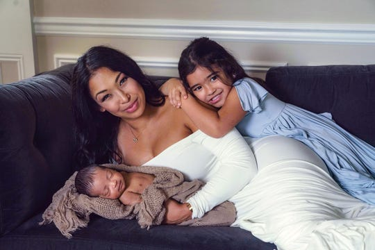 Thara Natalie Prashad-Jhooti laying on the couch with her daughter Ayva and son Aaryan.