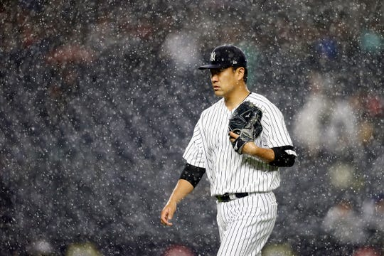 Masahiro Tanaka of the New York Yankees walks off the field as the tarp is put on the field for a rain delay against the Seattle Mariners at Yankee Stadium on May 07, 2019 in New York City.
