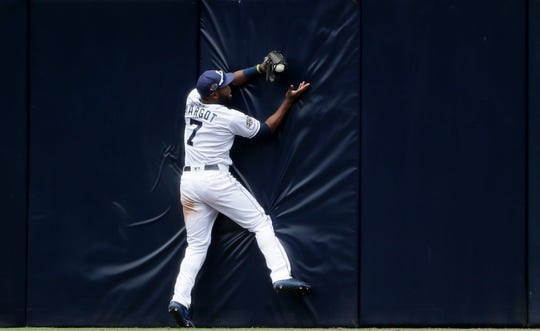 San Diego Padres center fielder Manuel Margot bobbles a catch at the wall off a hit for a double by New York Mets' Brandon Nimmo during the seventh inning of a game, Wednesday, May 8, 2019, in San Diego.
