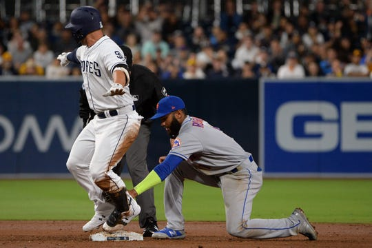 May 7, 2019; San Diego, CA, USA; New York Mets shortstop Amed Rosario (right) keeps the tag on San Diego Padres third baseman Ty France (left) throughout his slide as France comes off the bag during the second inning at Petco Park. France would be called out on the play. Mandatory Credit: Jake Roth-USA TODAY Sports