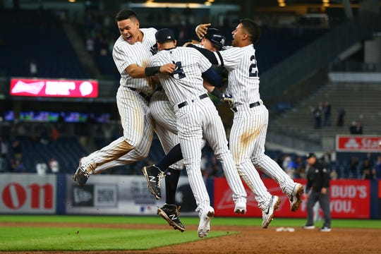 DJ LeMahieu of the New York Yankees is mobbed by his teammates after hitting a game-winning single in the bottom of the ninth inning against the Seattle Mariners at Yankee Stadium on May 07, 2019 in New York City. The Yankees defeated the Seattle Mariners 5-4.
