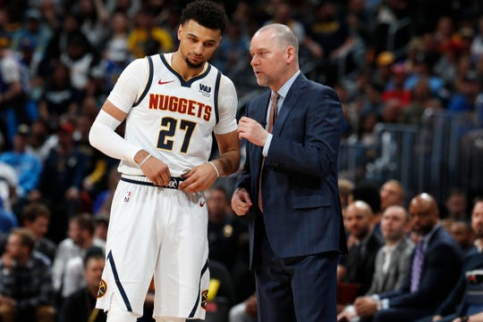 Denver Nuggets head coach Michael Malone, right, confers with guard Jamal Murray during a break in the action against the Portland Trail Blazers in the first half of Game 1 of an NBA basketball second-round playoff series Monday, April 29, 2019, in Denver.