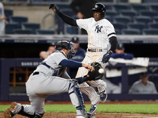 Seattle Mariners catcher Tom Murphy, left, tries to corral the throw as New York Yankees' Cameron Maybin runs home to score on a game-winning RBI single by DJ LeMahieu during the ninth inning of a baseball game, Tuesday, May 7, 2019, in New York. The Yankees won 5-4. (AP Photo/Kathy Willens)