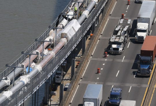 """Work crews renovate the """"barrels"""", the thick cables that hold up the roadway on the bridge that are comprised of thousands of thinner wires banded together, some of which are being replaced. The 592 suspender ropes, cables that are attached to the barrel cable are being replaced as well. This is on the north side of the bridge."""