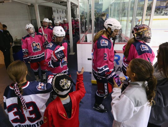 FILE - This photo from Oct. 25, 2015 shows members of the New York Riveters (currently the Metropolitan Riveters) of the National Women's Hockey League high-fiving fans while walking out for the third period against the Connecticut Whale at the Aviator Sports and Event Center in Brooklyn.