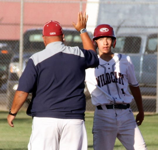 Junior Adrian Chavez receives a high-five from Deming High Head Coach Fernie Holguin after ripping a two-run triple in an 8-2 victory over Alamogordo last Friday at E.J. Hooten Park.
