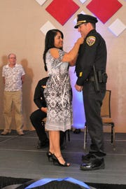 Lt. Chris Hughs is pinned on by his wife at the APD Promotion Ceremony Monday.