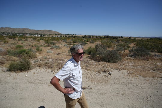 Thomas Fjallstam, organizer of the Joshua Tree Gateway Communities Vacation Rentals Association, walks in front of the proposed site of a 55-unit Airstream development in Joshua Tree.