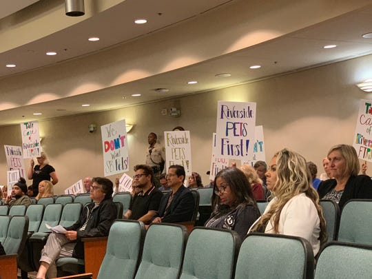 Demonstrators opposed to having Riverside County accept a contract to administer animal services to the City of San Bernardino hold up signs at a Riverside County Board of Supervisors Meeting in Riverside, Calif on May 7, 2019.