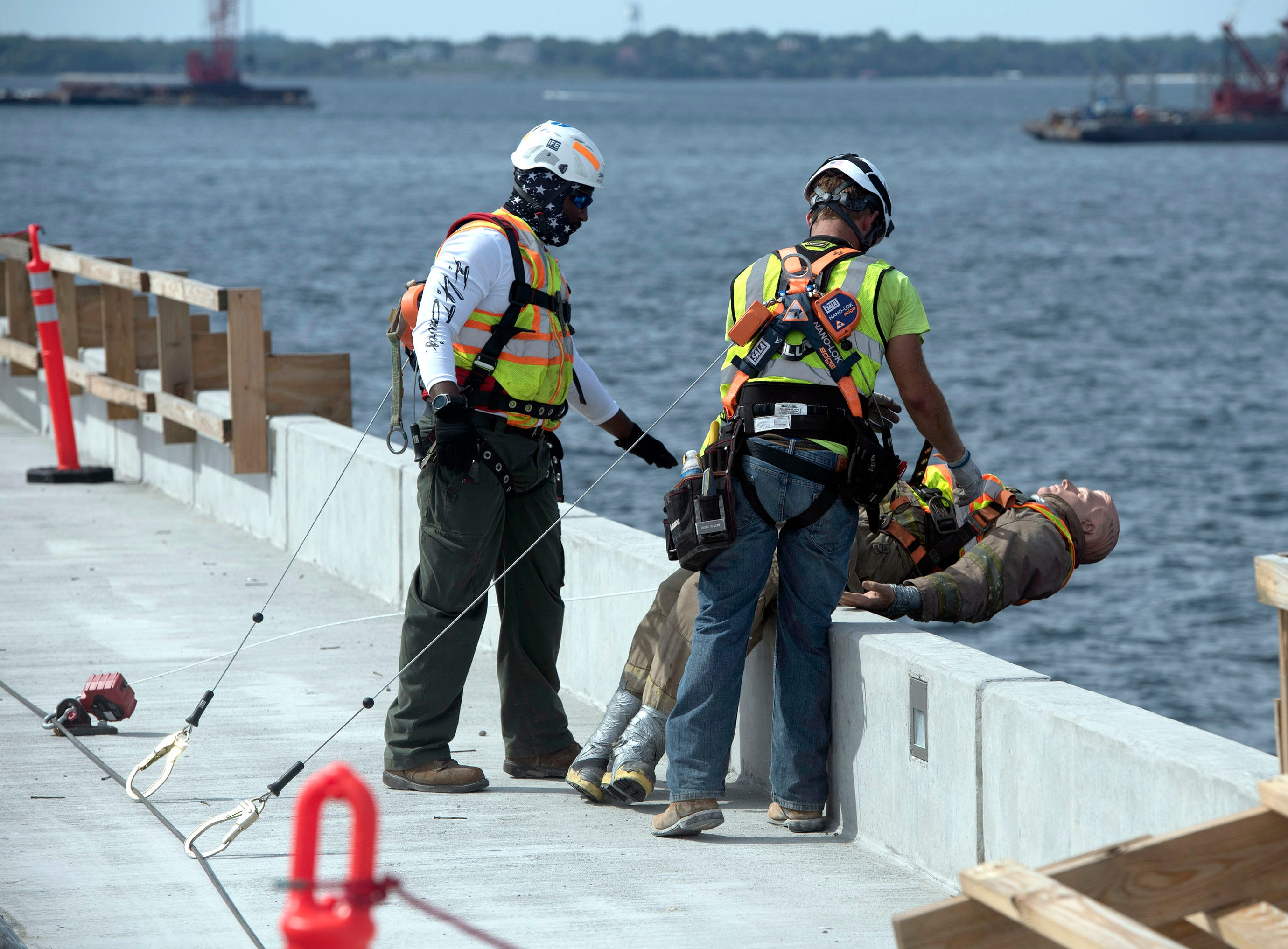 Skanska USA employees Marquis Meriweather and Reiley Werton work with members of the Pensacola Fire Dept., Escambia Fire Rescue, and the Gulf Breeze Volunteer Fire Dept. during a joint safety training exercise on the new Pensacola Bay Bridge under construction on Wednesday, May 8, 2019. The training exercise is part of the company's observance of National Safety Week.