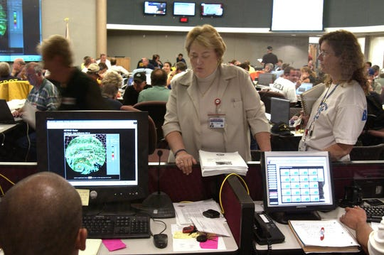 A 2005 file photo shows Janice Kilgore, then Escambia County Director of Public Safety, talking with Matt Lopez, then Chief of Emergency Management for Escambia County (lower left edge of photo) in the Emergency Operations Center on Sunday, July 10, 2005, as Hurricane Dennis approached Pensacola Beach.