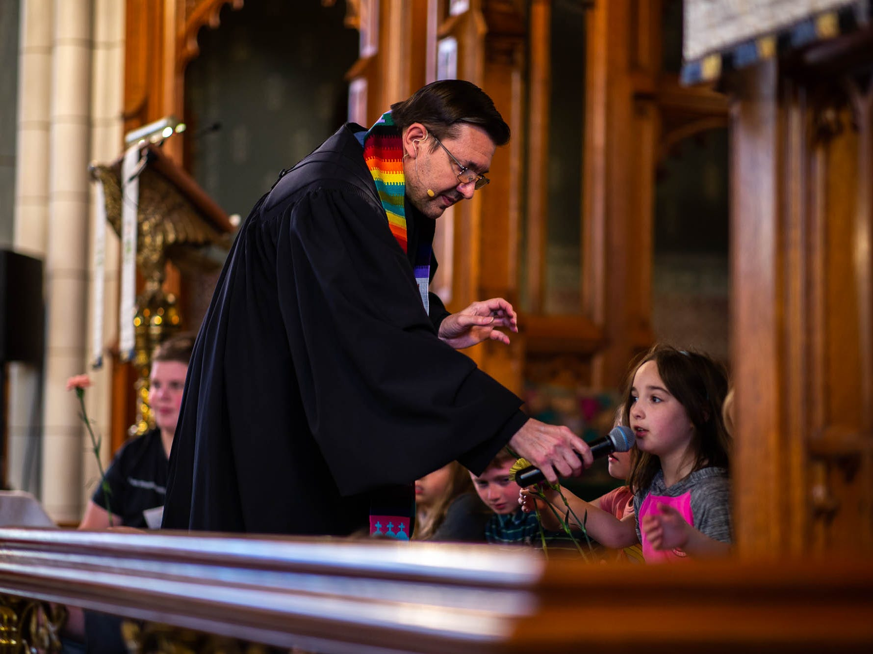 Reverend Russell Clark speaks with a child during a diversity service at the Emmanuel United Church of Christ, Sunday, April 7, 2019, in Hanover. Reverend Clark is the first openly gay pastor at the church.