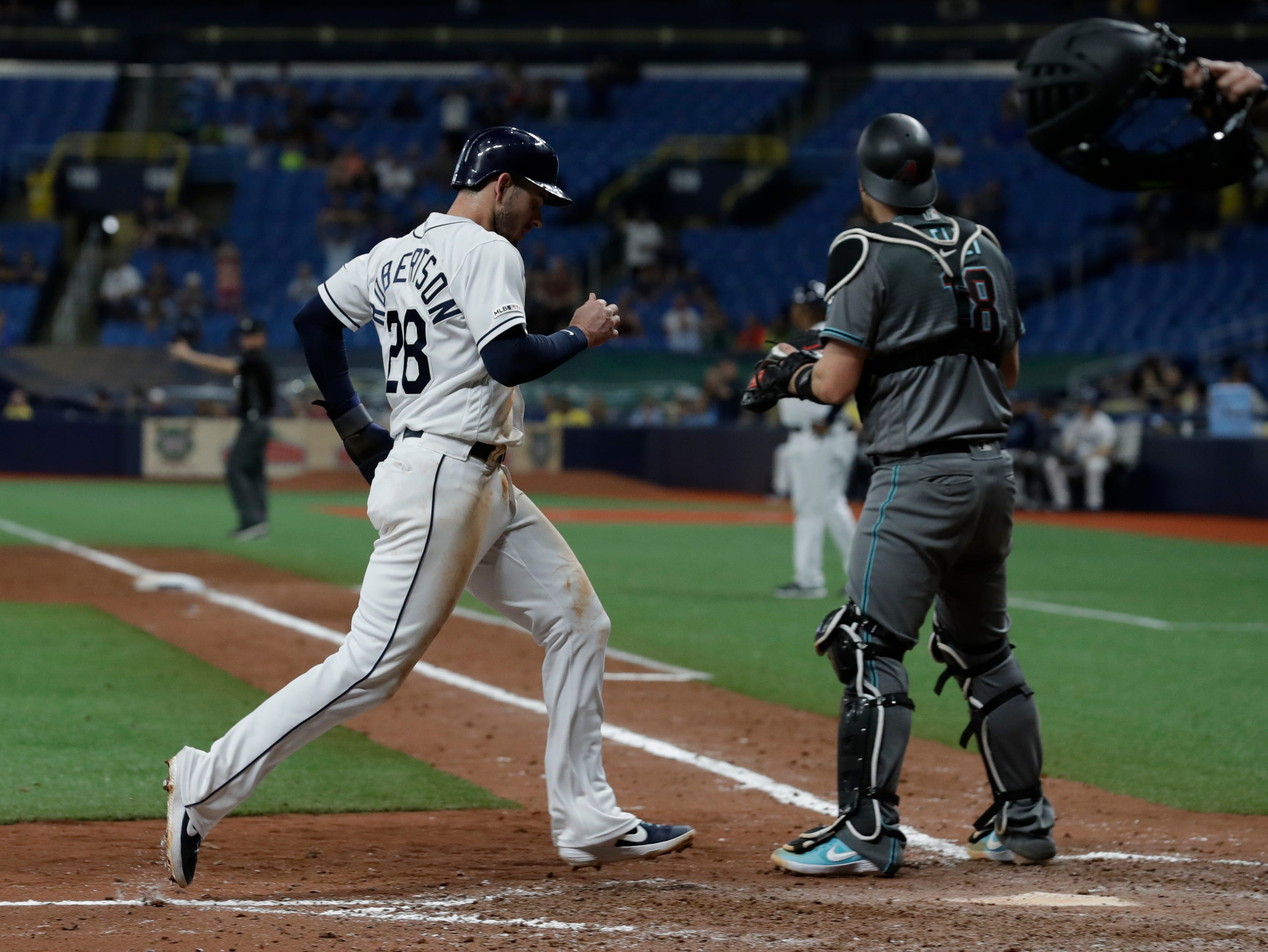 Tampa Bay Rays' Daniel Robertson (28) scores behind Arizona Diamondbacks catcher Carson Kelly on an RBI double by Mike Zunino during the seventh inning of a baseball game Tuesday, May 7, 2019, in St. Petersburg, Fla. (AP Photo/Chris O'Meara)