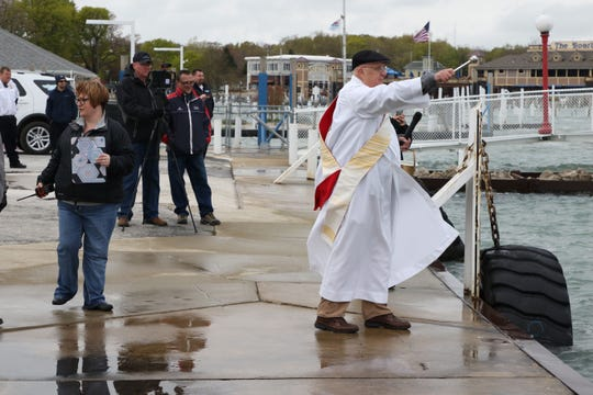 Deacon Mike Leahy uses an aspergillum to sprinkle holy water during the 2019 blessing of the fleet ceremony on Tuesday at Put-in-Bay.