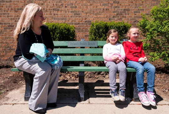 Millside Elementary principal Melissa Hanners, left, sits on a buddy bench dedicated to Dylan Carter with kindergarteners Olivia Elliott, 6, middle, and Savannah Ingles, 6, after lunch period Wednesday, May 8, 2019 on the school's playground. Dylan Carter was a kindergartener at Millside Elementary who passed away from brain cancer in July 2017.