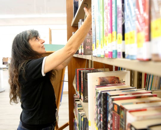 Pleasant Valley Free Library's clerk Linda Hanlon shelves books int he young adult fiction section inside the library's temporary location on May 7, 2019.