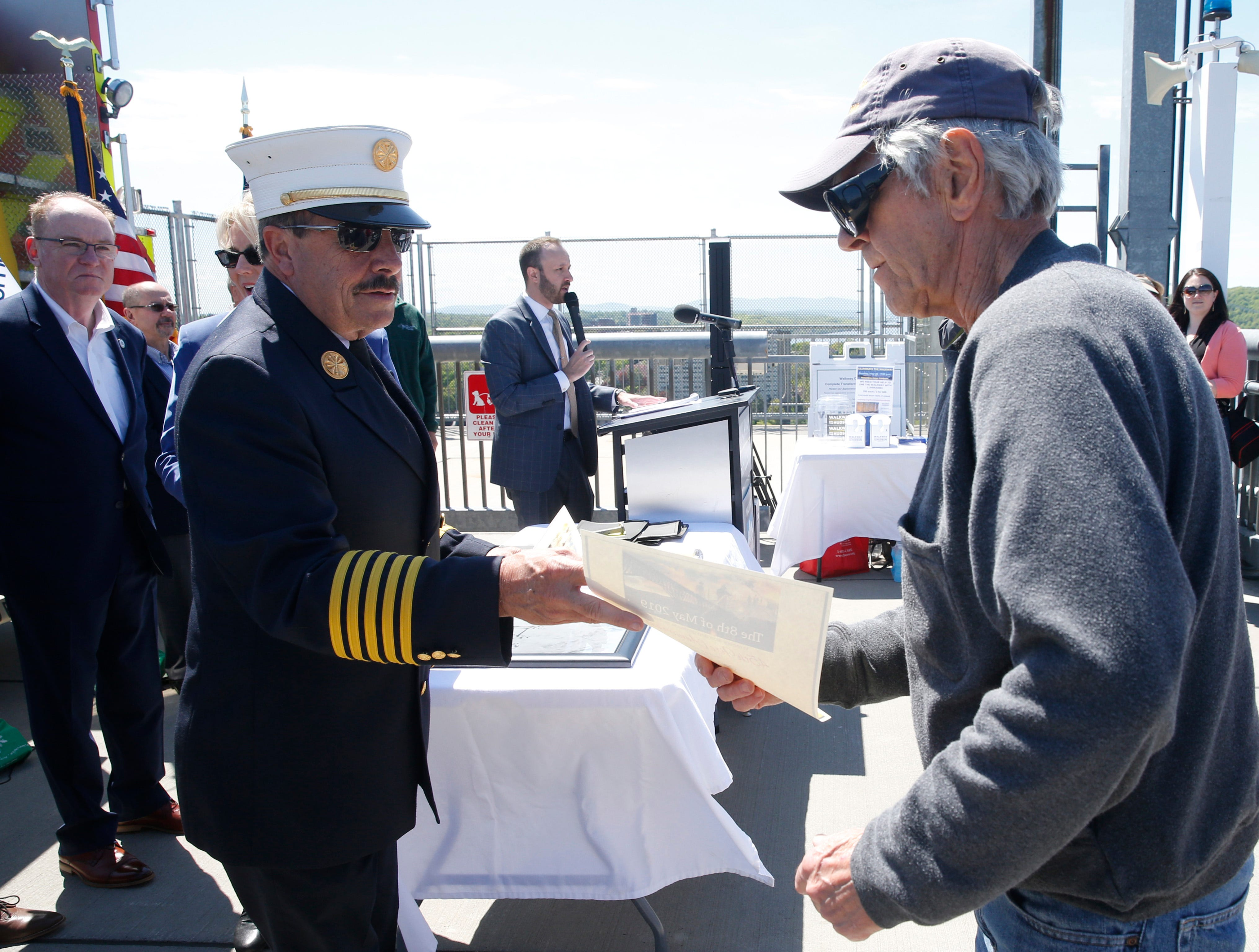 City of Poughkeepsie fire chief Mark Johnson gives a certificate to retired Poughkeepsie firefighter Roger Whitman during Wednesday's commemoration of 45th anniversary of the fire that engulfed the railroad bridge on May 8, 2019. Whitman was one of the city firemen who responded to the fire in 1974.