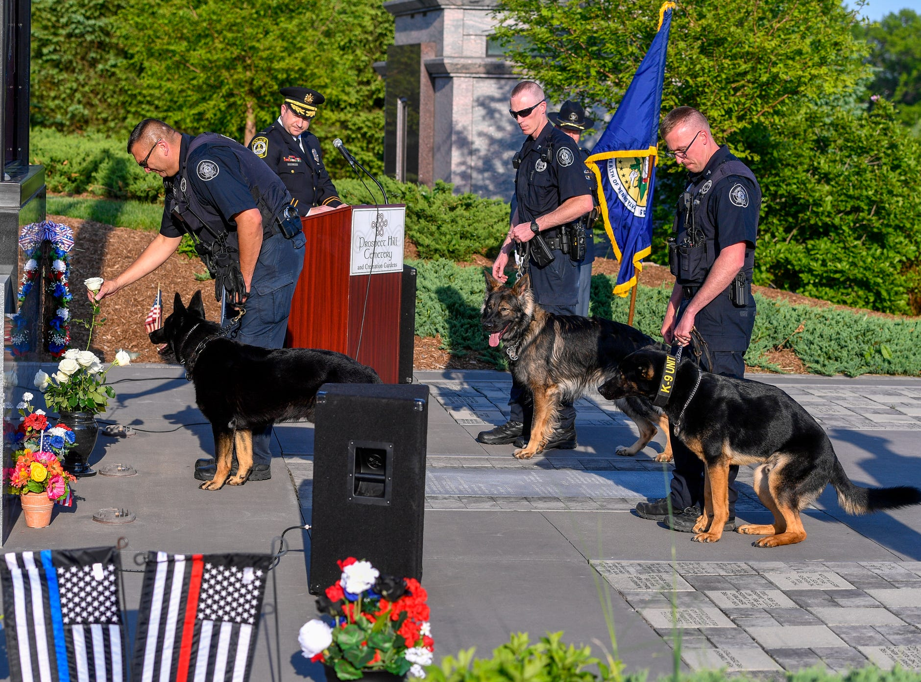 Members of the York County Sheriff's Office K9 Unit place a white rose at the Safekeepers Shrine in honor of K9 Lt. Lou during the Law Enforcement Community Remembrance event at Prospect Hill Cemetery,  Tuesday, May 7, 2019.