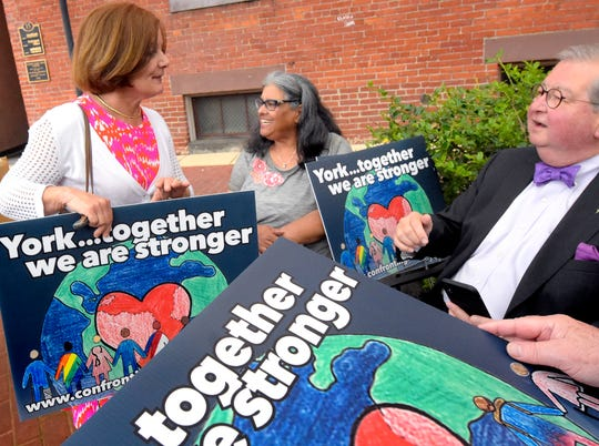 York County Commissioner Susan Byrnes, left, and York City Councilman Henry Nixon talk with Confronting Racism Coalition member Maggie Manning after a CRC press conference outside the Jewish Community Center's IDEAS Center in Cherry Lane Park Wednesday, May 8, 2019. During the event, members of the CRC shared its vision for creating equality in the York Community. Yard signs in support of the coalition were circulated after the event. Bill Kalina photo