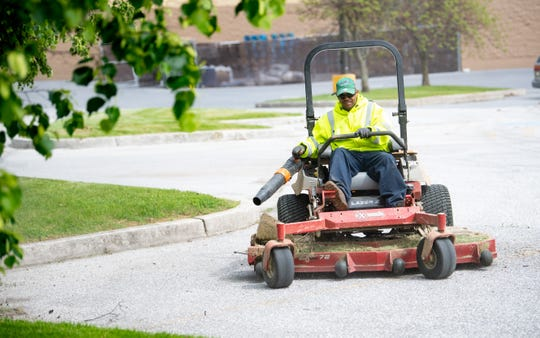 After cutting the grass, a worker makes sure to clean off the West Manchester Town Center parking lot, May 8, 2019.